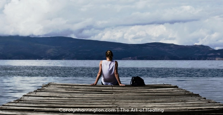 Woman sitting at the end of a pier