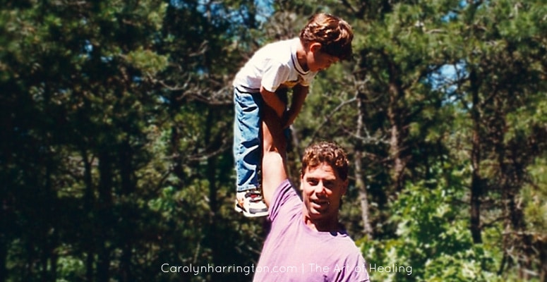 Man holding son up with one arm.